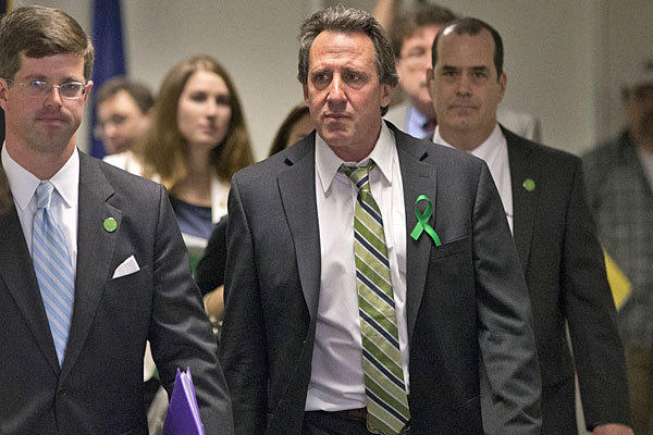 Neil Heslin, center, whose 6-year-old son Jesse was killed in the mass shooting in Newtown, Conn., arrives with other victims' families to meet privately with senators on Capitol Hill.