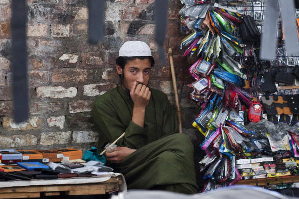 Pakistani vendor Mohammad Ishaq, 18, a supporter of cricket legend-turned politician Imran Khan, waits for customers in Islamabad, Pakistan. A larger number of young Pakistanis believe the country should be governed by Islamic law or military rule rather than democracy, according to a recent survey.
