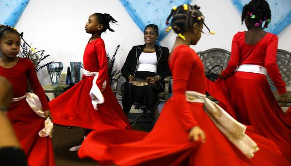 On a Sunday in March, Jacqueline Kennedy-Harris watches dancers perform for a service at her storefront church in Chicago's Englewood neighborhood.