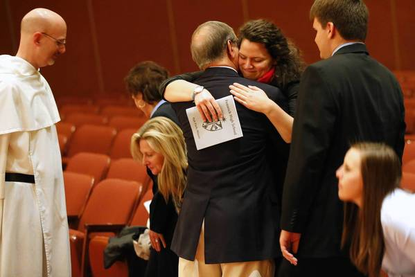 Regina Smedinghoff hugs Andy Arellano, a speech teacher at Fenwick High School, after a memorial Mass for Smedinghoff's sister, Anne, at the Catholic school on Tuesday.