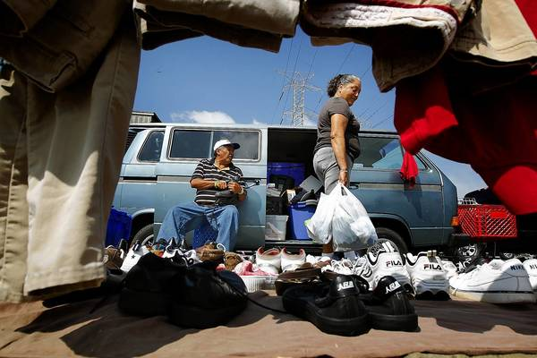 Jesus Navarro, left, looks on as a customer examines the wares in his outdoor vending area in Watts. Los Angeles County officials are looking for ways to crack down on the proliferating informal flea markets.