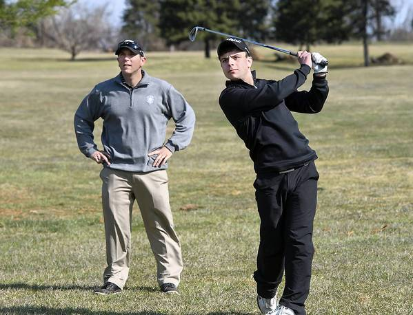 Golf director Paul Viola (left) gives pointers to Northampton High School golfer Evan Notaro, 18, of Northampton, at the Bethlehem Municipal Golf Course on Sunday, April 7, 2013.