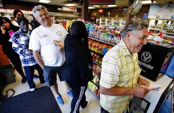 Rafael Moreno picks Powerball numbers Monday as others form a line at Bluebird Liquor in Hawthorne. California is the latest state to participate in Powerball.