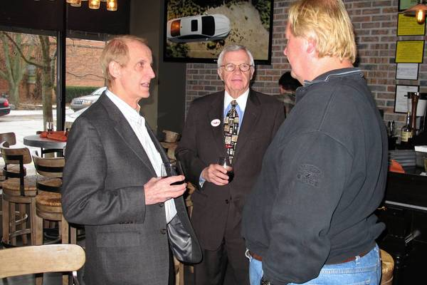 Gene Greable, at left, talks to supporters at his election party at Trifecta wine bar. Greable won the race for village president, according to unofficial results.