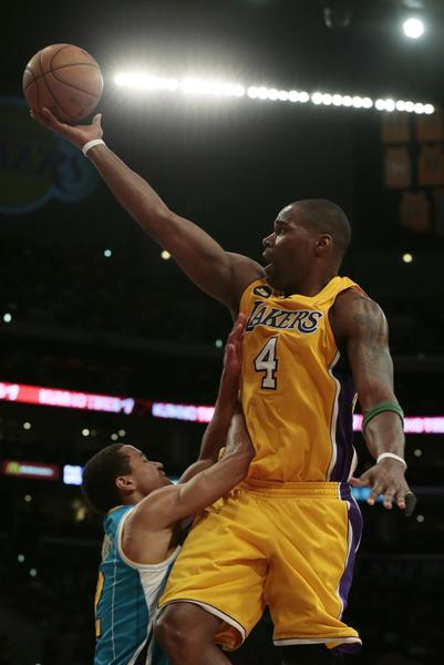 Lakers forward Antawn Jamison is fouled by New Orleans Hornets guard Terrel Harris as he drives to the basket.