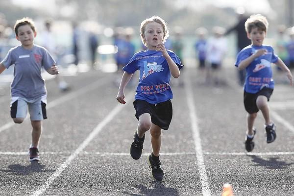 Eastbluff Elementary's Luke Miller, 6, center, sprints to the finish line in a 50-meter dash, Division 06, during Newport-Balboa Rotary Club's Youth Track Meet of Champions held at Corona del Mar High on Friday. Chester placed second in this heat.