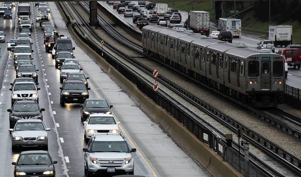 A CTA Blue Line train moves past both inbound and outbound Kennedy Expressway traffic after a morning rainstorm. Rain is expected off and on throughout the day.