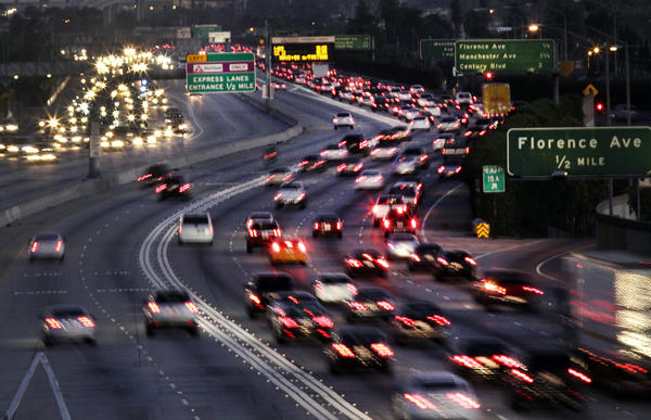 Traffic on the 110 Freeway southbound from Slauson Avenue during rush hour. The toll lanes on the left are relatively clear; other lanes are not.