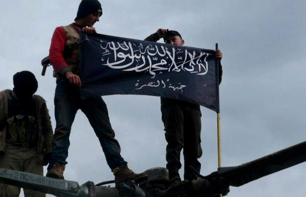 This image by a citizen journalist provided by Edlib News Network, which has been authenticated based on its contents and other Associated Press reporting, shows rebels from Al Qaeda-affiliated Al Nusra Front waving their brigade flag on the top of a Syrian air force helicopter captured by the rebels, in Idlib province, northern Syria.