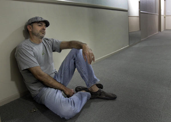 Vyktor Emilio Arce sits in the hallway of the Hollywood apartment where authorities say Nattie Kennebrew attempted to shoot him after killing a handyman.