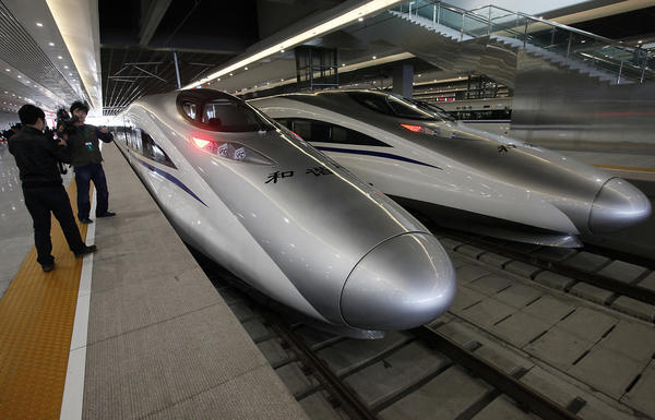 A journalist photographs bullet trains on a new high-speed railway linking Shanghai and Hangzhou in 2010.