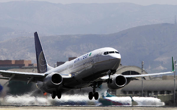 An airliner lifts off from John Wayne Airport before beginning its steep climb