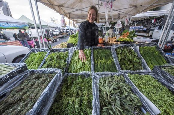 Andrea Crawford of Kenter Canyon Farms sets up a display of a dozen herbs grown in Fillmore.