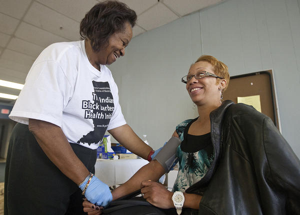 Nurse Betty Greene, left, checks the blood pressure of South Bend resident Anita Nelson during last years Indiana Black Barbershop Health Initiative at Image Hair Studio in South Bend. This years event is Saturday. (South Bend Tribune/ROBERT FRANKLIN)