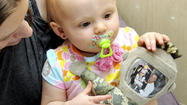 Though 13-month-old Harley Ann Lubic may not see her Army staff sergeant father for long stretches of time, she won't forget his face thanks to a special doll.