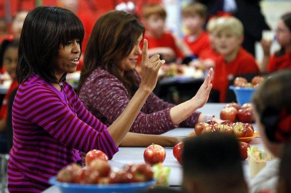 Strict lunch rules may help students maintain their weight, a study suggests. Above, First Lady Michelle Obama talks to Mississippi students at lunchtime this year.