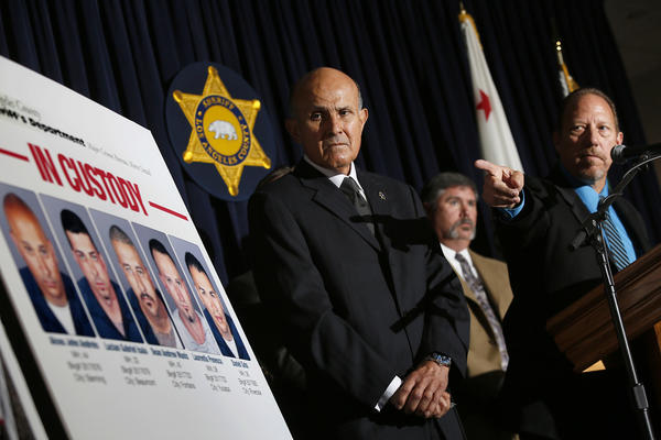Los Angeles County Sheriff Lee Baca, left, looks at booking photos of suspects in a series of bank heists in the San Gabriel Valley. Five men were arrested last Friday in connection with the burglaries.