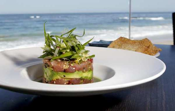 The ahi tuna tartar with avocado, scallions, fresh ginger and cucumber broth is an appetizer favorite at Splashes in the Surf & Sand Resort.