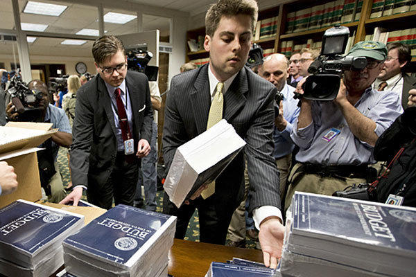 Copies of President Obama's budget plan for fiscal year 2014 are distributed to Senate staff on Capitol Hill.