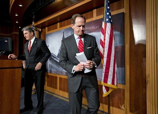 Sens. Pat Toomey (R-Pa.), right, and Joe Manchin (D-W.Va.) finish a news conference in Washington on Wednesday announcing that they have reached a compromise on background checks for gun buyers.