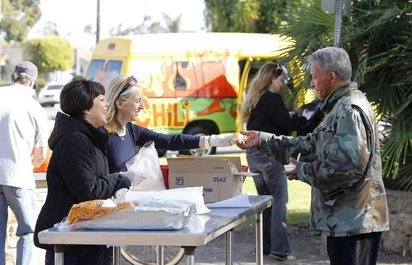 Temre Vouga and Fatima Bergquist serve hot chili and bread to a visitor of the Orange County Rescue Mission's Chili Van during a visit to Lake Park on 11th and Main streets.