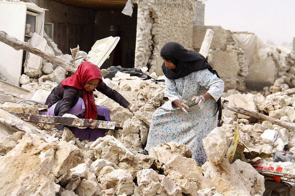 Iranians search through the rubble in the southern town of Shanbe.