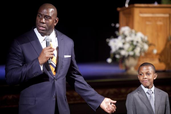 """Earvin """"Magic"""" Johnson speaks to a crowd at the Temple Theatre in Saginaw, Mich., on Tuesday, April 9, 2013 for the Magic of a Promise event, in which Johnson donated $100,000 to Saginaw Promise, helping pay for local students' college tuition. Over $100,000 more was raised when Johnson auctioned off promised appearances and flying people out to LA for Dodgers and Lakers games. He answered questions from the crowd, including Daniel Webster, right, age 11, from Handley Elementary School, who he teased for being so confident while speaking with him. (AP Photo/The Saginaw News, Clay Lomneth) ** Usable by LA and DC Only **"""