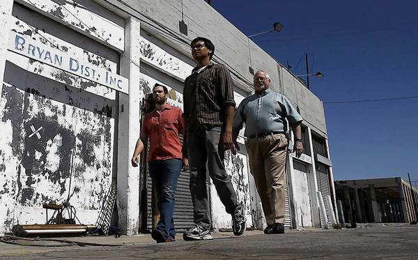 Electric Dusk Drive-In owners Eric Heusinger, left, and Daryl Semira, center, walk with their new landlord, Peter Fleming, at the former site of the San Pedro Street Produce Market, where a project that may include a college, hotel, offices and apartments is planned.