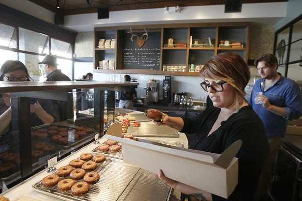 Amanda Prettyman boxes up doughnuts during a media event for Sidecar Doughnuts & Coffee in Costa Mesa on Wednesday.