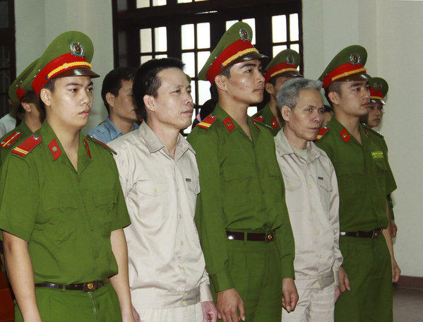 Doan Van Vuon, second from left, and his brother Doan Van Sinh, fourth from left, stand trial in Haiphong, northern Vietnam.