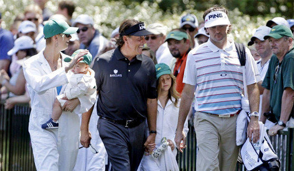Phil Mickelson walks with Bubba Watson and his wife Angie and their son Caleb during the par three competition before the Masters golf tournament.