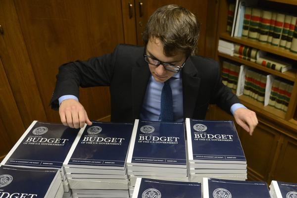 A staffer with the U.S. Senate Budget Committee distributes copies of President Obama's FY2014 budget to Congressional staff members, on Capitol Hill in Washington, D.C.