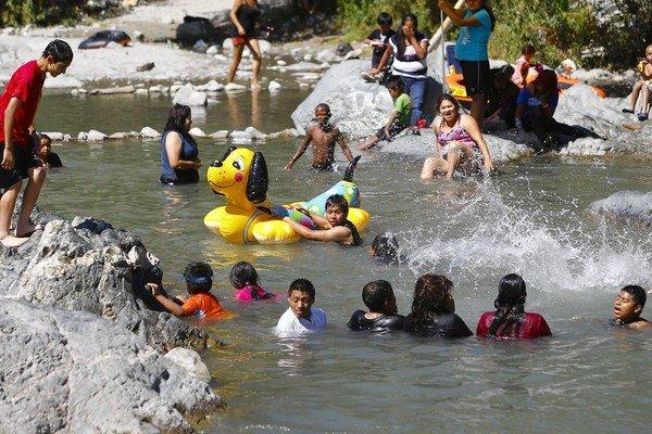 Visitors splash in the east fork of the San Gabriel River. The San Gabriel range, which is managed by the U.S. Forest Service, is prone to fires and is visited by enormous weekend crowds that bring vandalism, drug deals, car burglaries, trash, illegal campfires and emergency rescues.