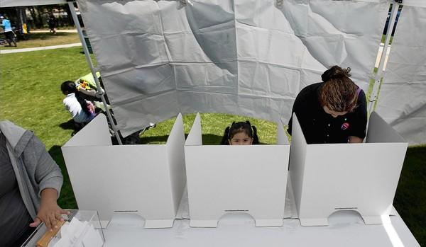 Under a white tent, parent Edith Medrano, with 3-year-old daughter Graidy, votes on who will operate 24th Street Elementary School. Parents chose a collaboration between L.A. Unified and a charter operator.