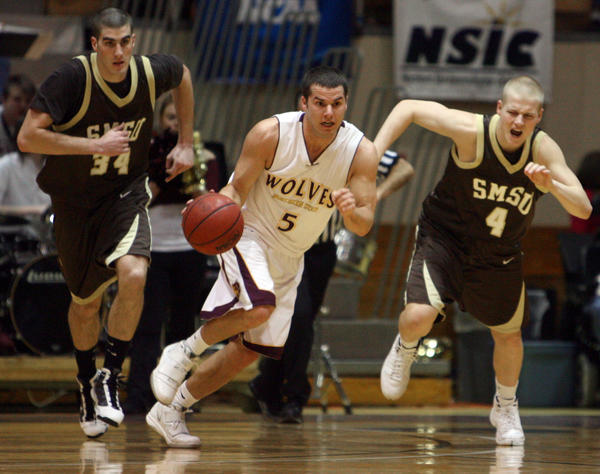 Northern State University's Derek Hoellein pushes the ball up the floor ahead of Southwest Minnesota State's Scott Roehl, left and Trent Carlson, right, during Saturday night's game at Wachs Arena. photo by john davis taken 2/27/2010