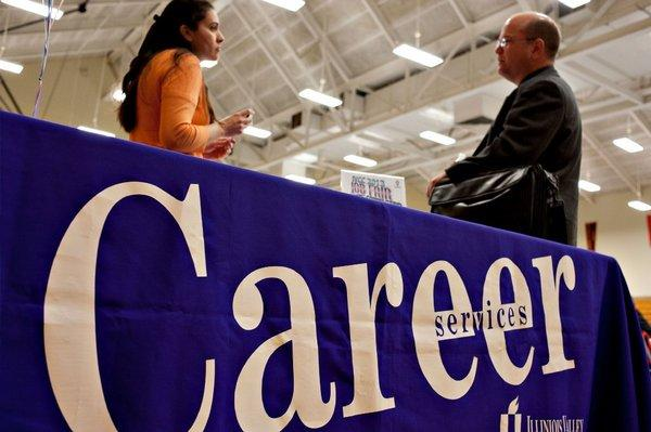 A job seeker, right, talks with an Illinois Valley Community College career advisor at a job fair in Oglesby, Ill.