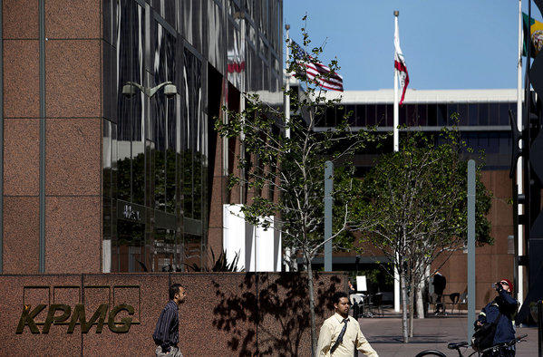 Pedestrians walk past the offices for the accounting firm KPMG LLP in Los Angeles.