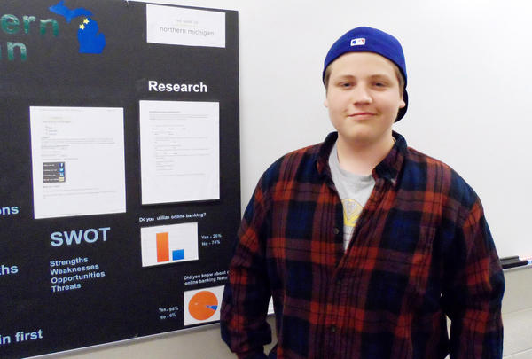 JAMIE BAUMANN/NEWS-REVIEW.Petoskey DECA student Julian Ruemenapp shows his project representing a marketing plan to increase customer use of online banking for the Bank of Northern Michigan. He won in the financial operation report category at the DECA state competition..