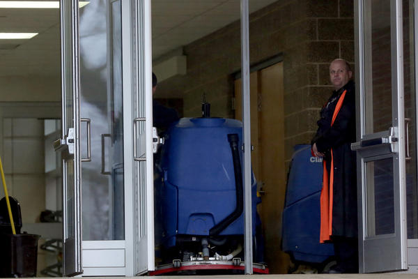 A police officer guards a door at Wheaton North High School where a small fire broke out in a classroom as a teacher was setting up a science experiment, officials said. No injuries were reported.