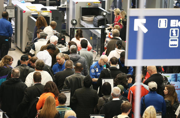 People wait in line for a security check at O'Hare International Airport.
