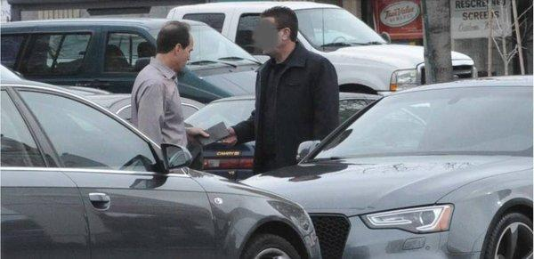 KPMG partner Scott London, left, is shown in an FBI photograph allegedly accepting a $5,000 cash bribe from Bryan Shaw earlier this year. Federal prosecutors have charged London with providing Shaw inside information on two California companies, Herbalife Ltd. and Skechers USA Inc.