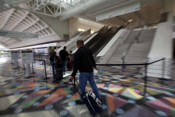 Travelers walk toward the security check-in at Ontario International Airport.