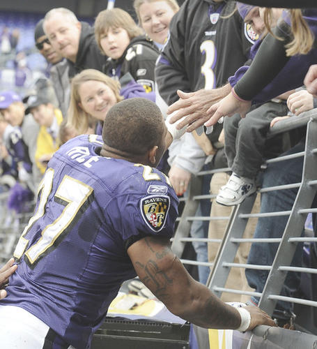 Ravens running back Ray Rice hands his gloves to a young fan in the stands after the game.