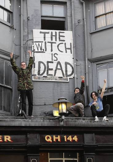 "People cheer in front of a London banner displaying the message ""The Witch is Dead"" after the death of Margaret Thatcher."