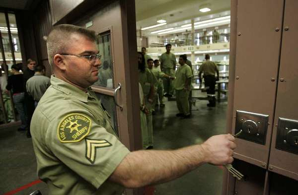 A sheriff's deputy locks down inmates in a cellblock at the North County Correctional Facility at the Pitchess Dentention Center in Castaic in 2006.
