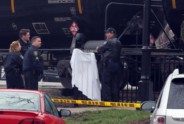 Police investigate at the scene where a Burlington Northern freight train struck and killed a pedestrian, near Burlington and Kensington Avenue in LaGrange, Ill., today