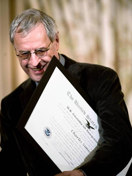 Charles Simic carries an award away during a naturalization ceremony at the U.S. State Department February 28, 2008 in Washington, DC.