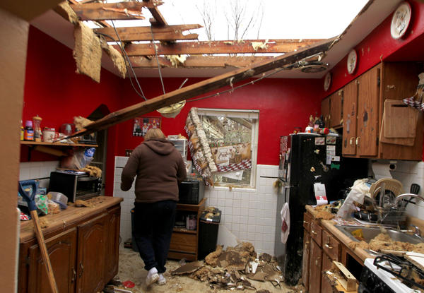 Karla Buneta walks through her storm-damaged kitchen Thursday in Hazelwood, Mo.