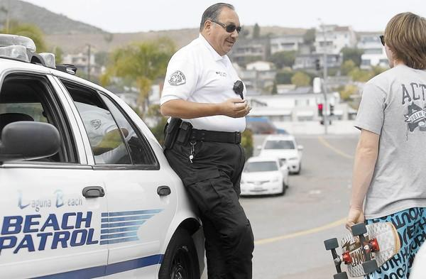 Laguna Beach Civilian Officer Fred Casas, center, informs a young adult of the city's helmet law for skaters on March 25.