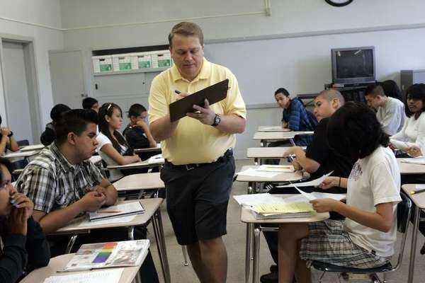 Brian York, algebra teacher at Monroe High School in North Hills, checks home work while students solve a problem in his summer school class in 2008. Monroe will be one of 16 high schools to offer credit recovery classes this summer.